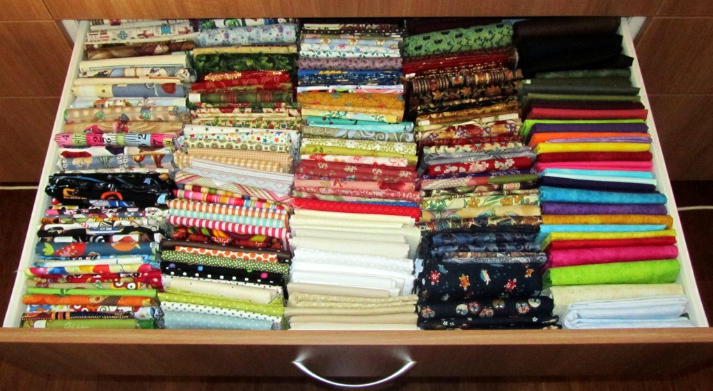 A drawer full of neatly folded fabrics.