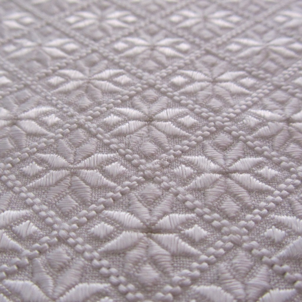 Detailed view of floral motifs covering the central area of the whitework panel.