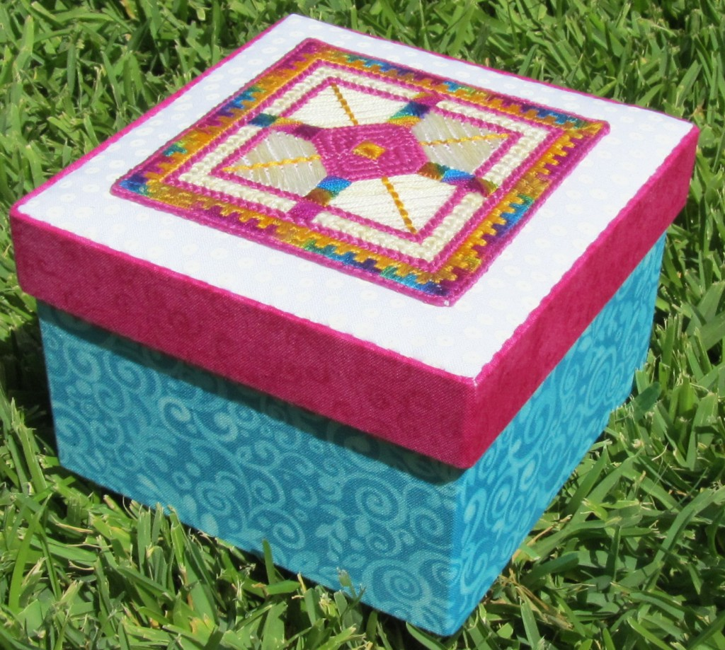 Fabric covered box topped with geometric canvaswork design. Completed size - 14cm x 14cm.
