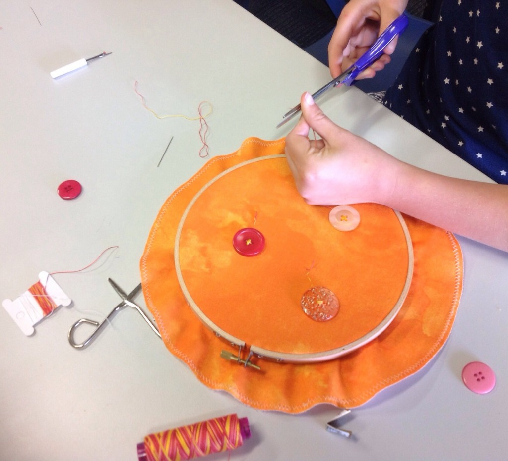 Learning to sew on buttons whilst creating an embroidery hoop wallhanging.
