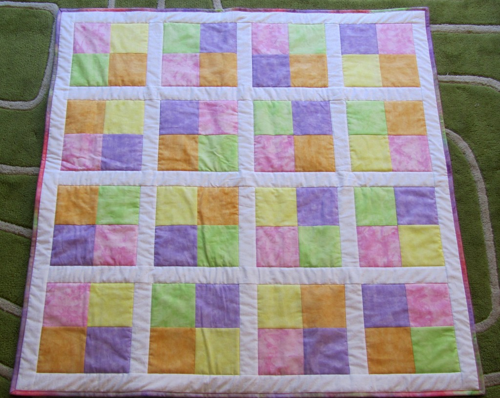 A simple quilt made for foster children from donated squares of fabric.